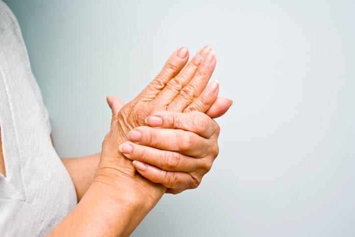 Paziente che si massaggia la mano colpita da artrtite reumatoide.