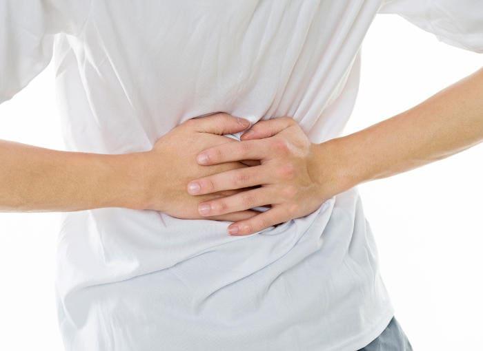 Primo piano di un giovane che si tiene la pancia a causa di dolori addominali