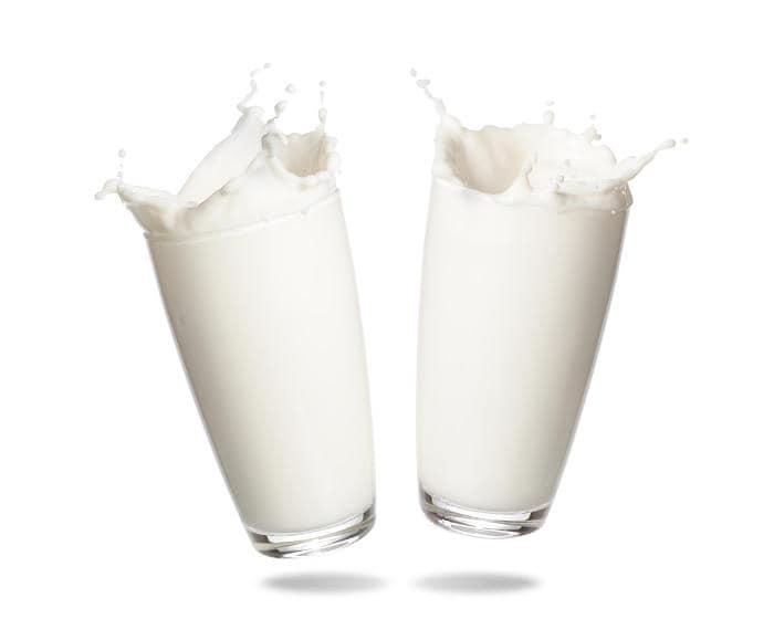 Due bicchieri di latte che schizzano dappertutto