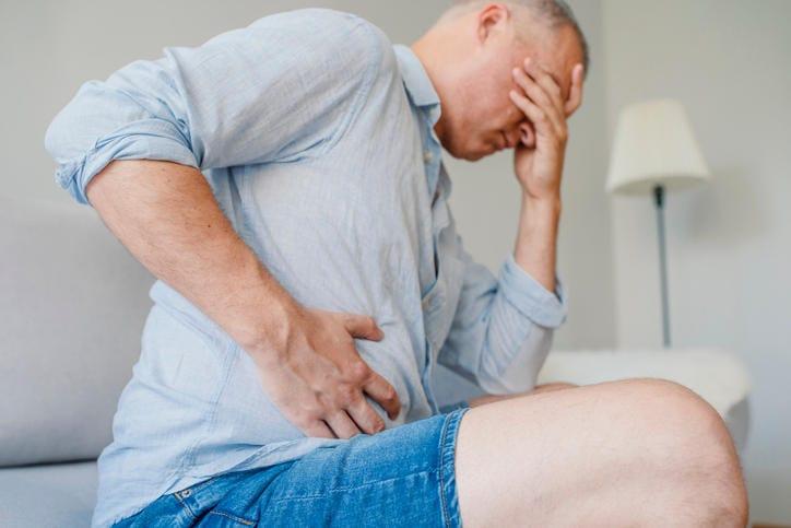 Uomo colpito da gastroenterite che si tocca la pancia