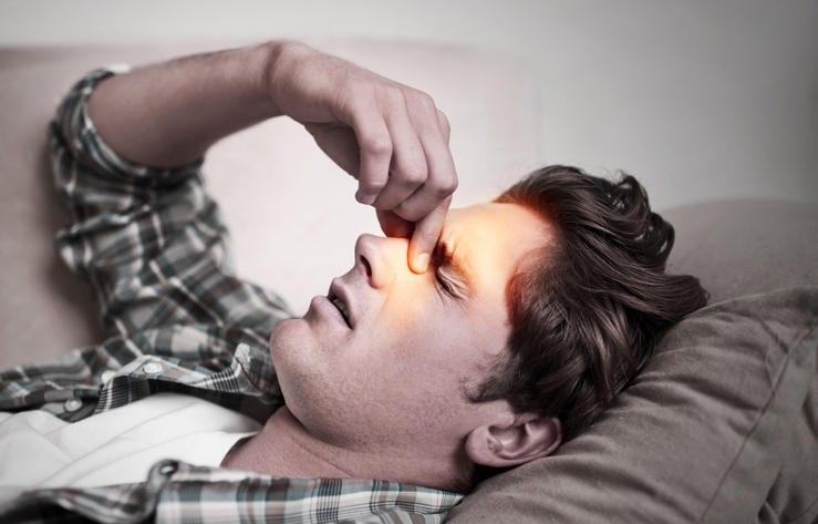 Uomo sdraiato sul letto, che si tocca la regione dei seni nasali a causa del dolore da sinusite