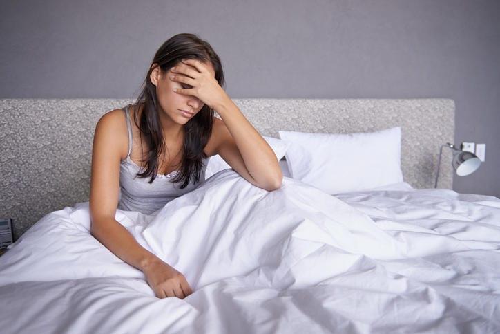 Donna sofferente nel letto affetta da fibromialgia