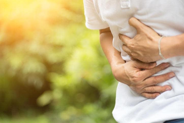 Mani di uomo avvolto attorno all'addome a causa di nausea e dolori da virus intestinale