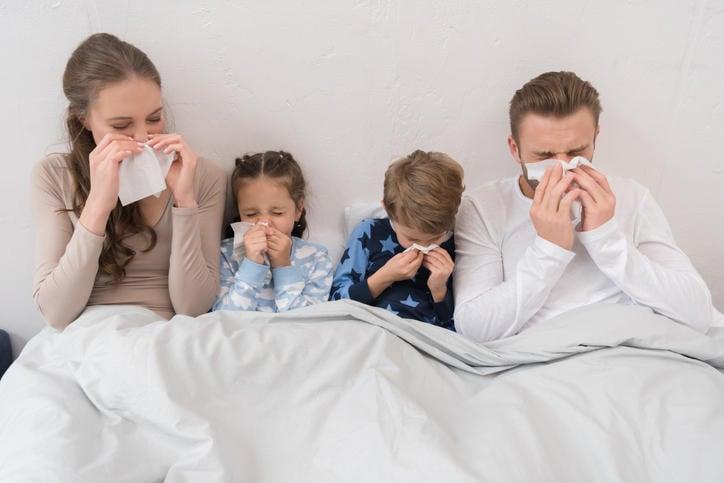 Famiglia a letto nell'atto di soffiarsi il naso a causa del raffreddore