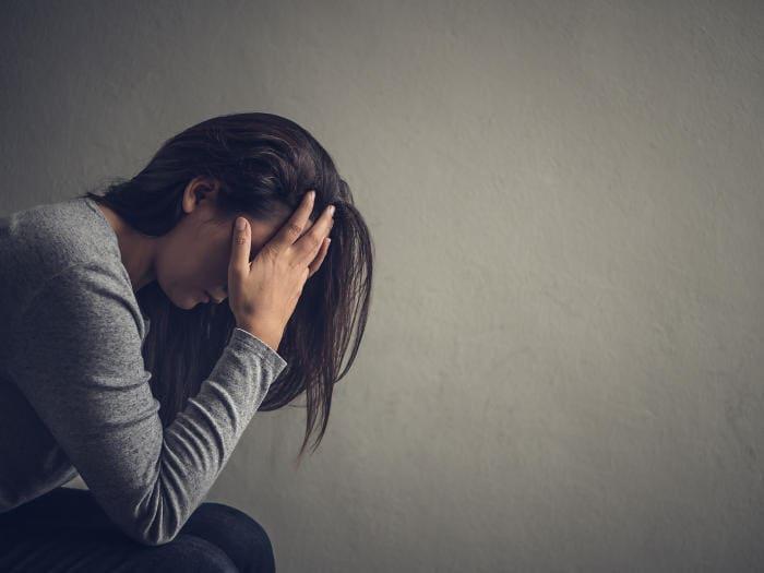 Donna con la testa tra le mani a causa di depressione