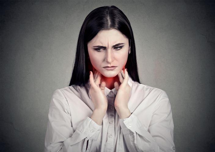 Donna che si tocca la gola a causa del dolore dovuto alla mononucleosi