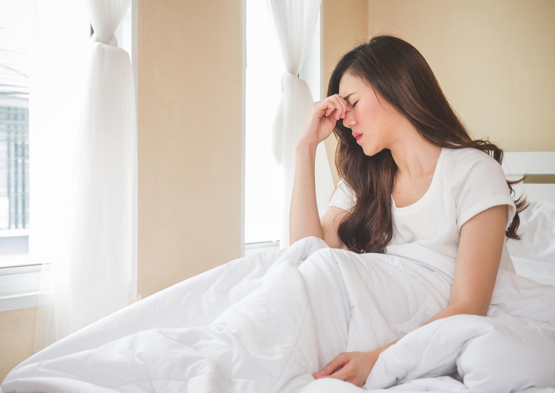 Donna che manifesta vertigini alzandosi dal letto