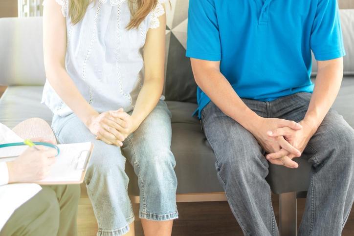 Fotografia di una coppia seduta in attesa della visita dermatologica