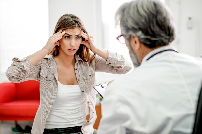 Giovane donna preoccupata dal dolore alla testa che parla con il medico