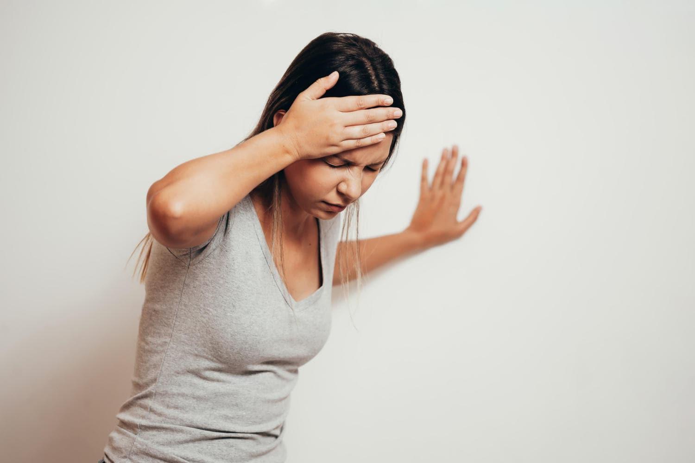 Donna che soffre di vertigini e si appoggia al muro