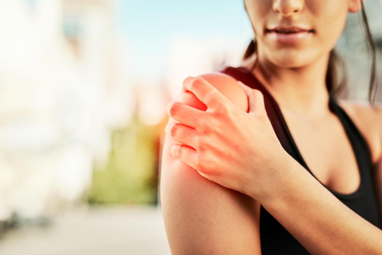 Ragazza che si tocca la spalla a causa di dolore