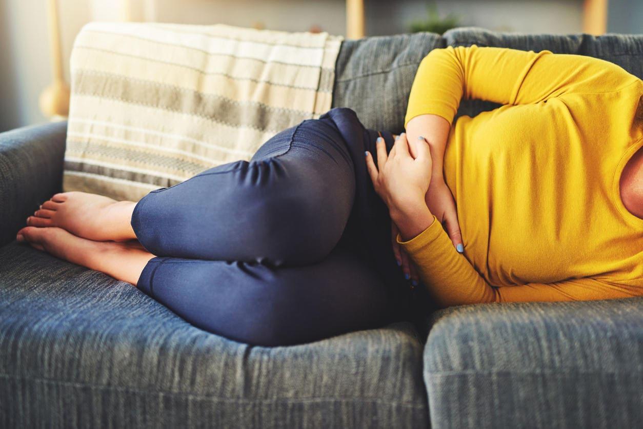 Donna sdraiata sul divano a causa di dolori da endometriosi