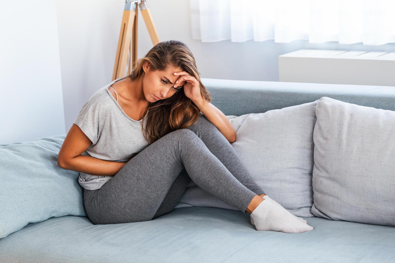 Donna sul divano sofferente di dolore pelvico