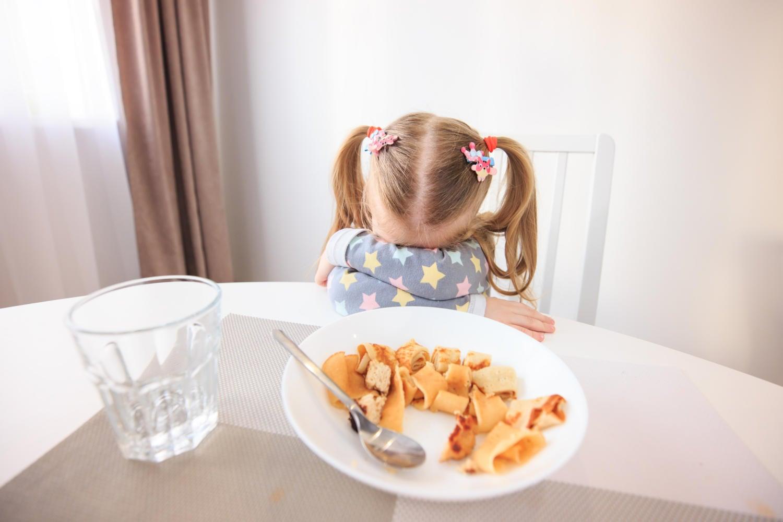 Bambina che rifiuta un piatto di pasta