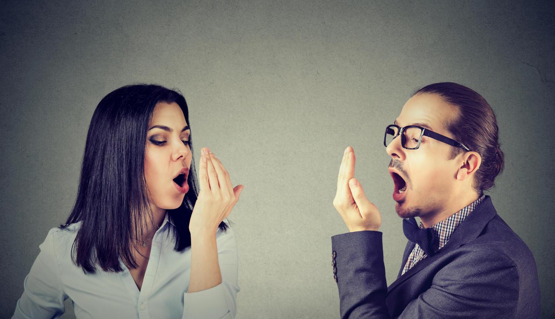 Un uomo e una donna che cercano di verificare l'alito con la mano a conchetta