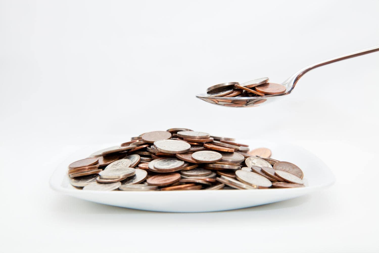 Piatto e cucchiaio pieno di monete