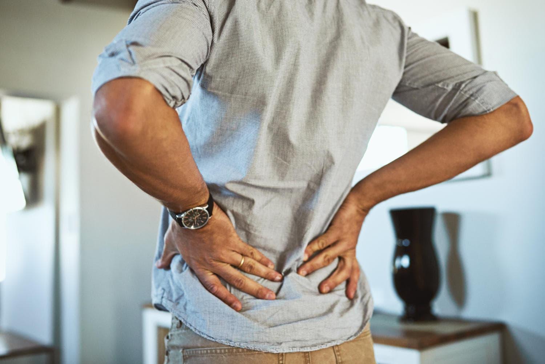 Uomo che si tocca la parte bassa della schiena a causa di dolore