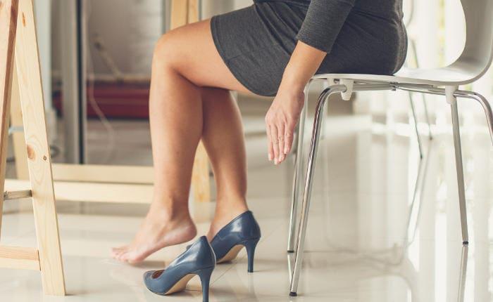Primo piano delle gambe di una donna, che accusa gonfiore tanto da sentire la necessità di togliersi una scarpa