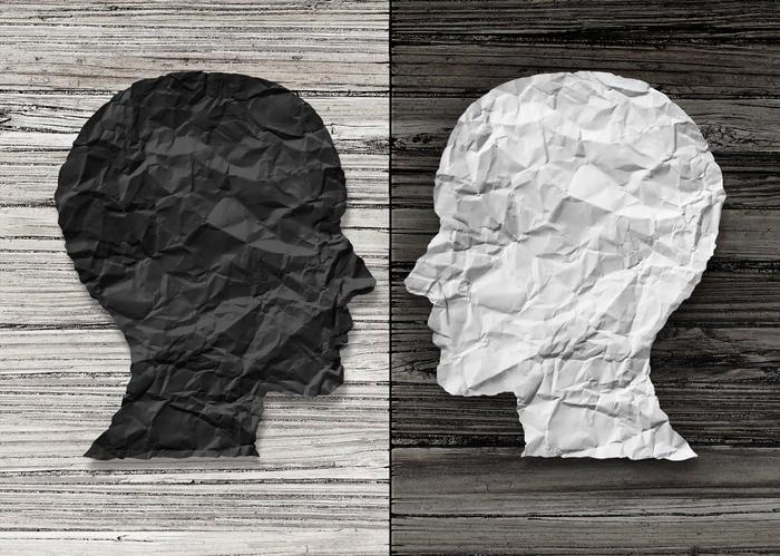 Due figure stilizzate di testa umana, rispettivamente bianco su nero e viceversa.