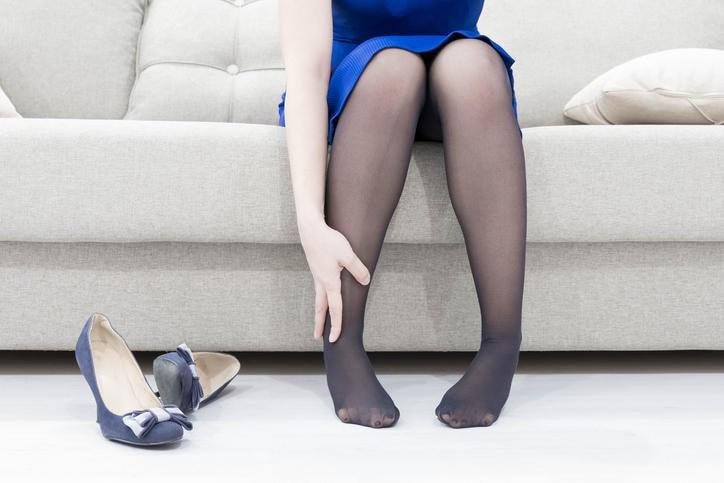 Primo piano delle gambe di una donna, mentre le tocca a causa dei disturbi da insufficienza venosa cronica