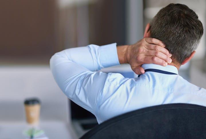 Uomo fotografato da dietro, che si tocca il collo a causa di dolore