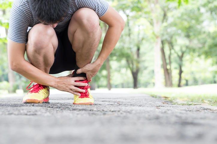 Sportivo che si tocca la caviglia a causa di una tendinite