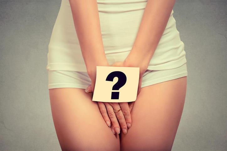 Primo piano della regione pelvica di una donna, con un cartella con disegnato un punto interrogativo