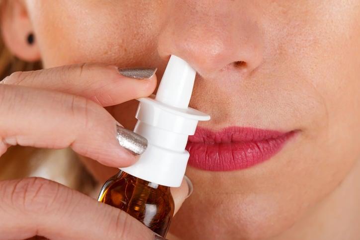 Donna nell'atto di spruzzare cortisione spray nel naso
