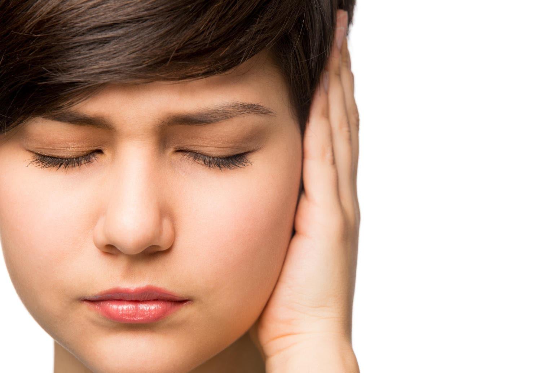 Donna che si tiene l'orecchio a causa del dolore