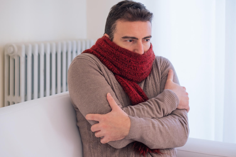 Uomo seduto sul divano che avverte freddo e brividi