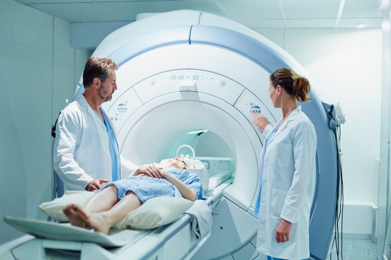 Paziente sdraiato sul lettino della risonanza magnetica assistito da due medici