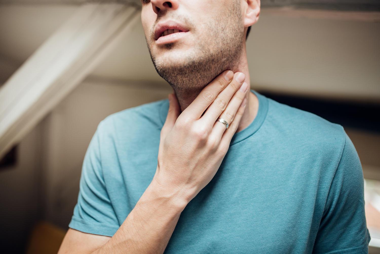 Uomo che si tocca la gola per la presenza di catarro