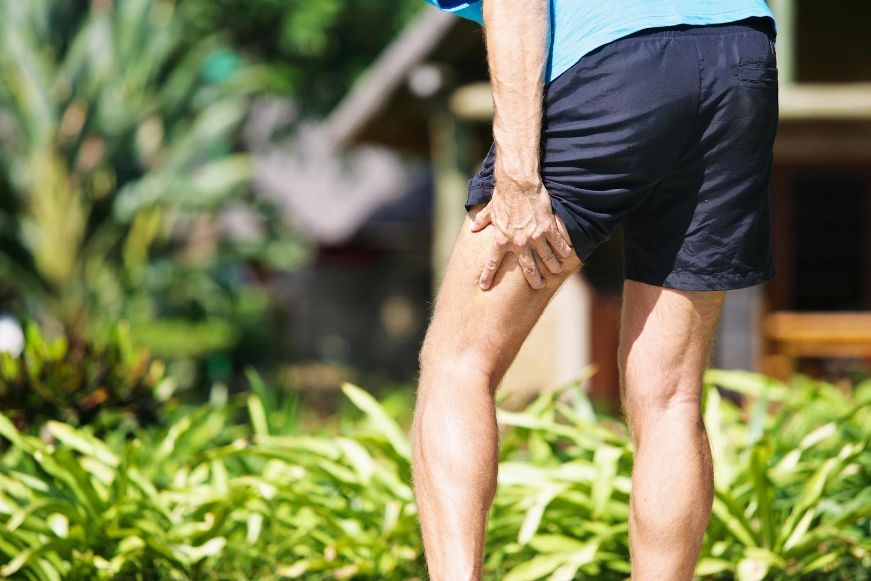 Uomo che si tocca la parte posteriore della coscia a causa di uno stiramento