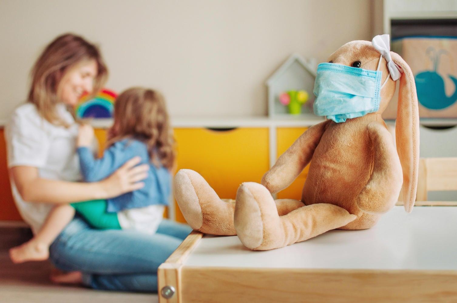 Coniglietto di peluche con mascherina, sullo sfondo mamma e bambina che giocano