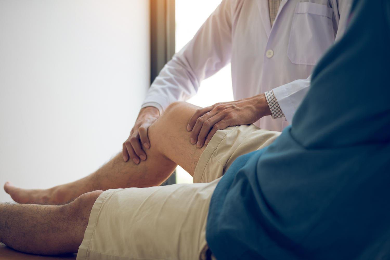 Medico che visita un paziente, valutandone la forza nella gamba