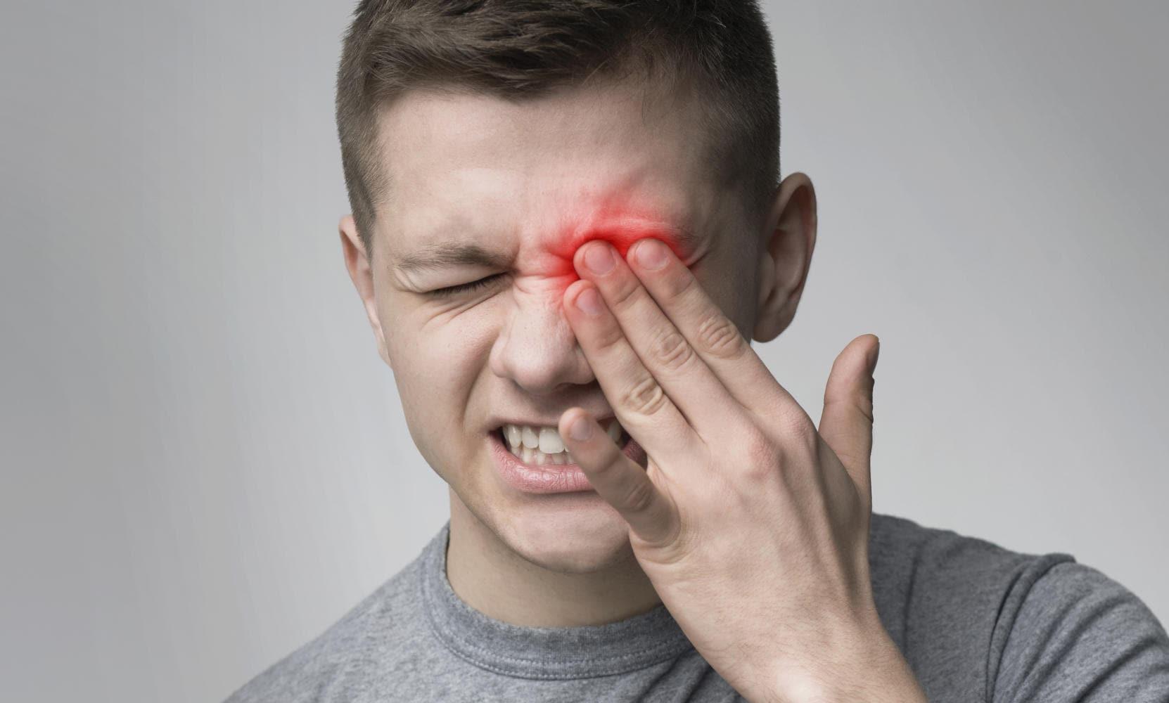 Uomo che si tocca l'occhio sinistro a causa di dolore