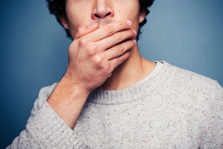 Uomo che si copre la bocca