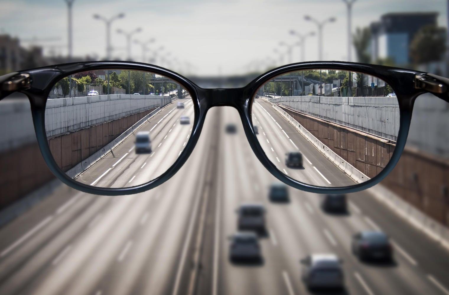 Immagine offuscata, con occhiali in primo piano e nelle lenti vista nitida