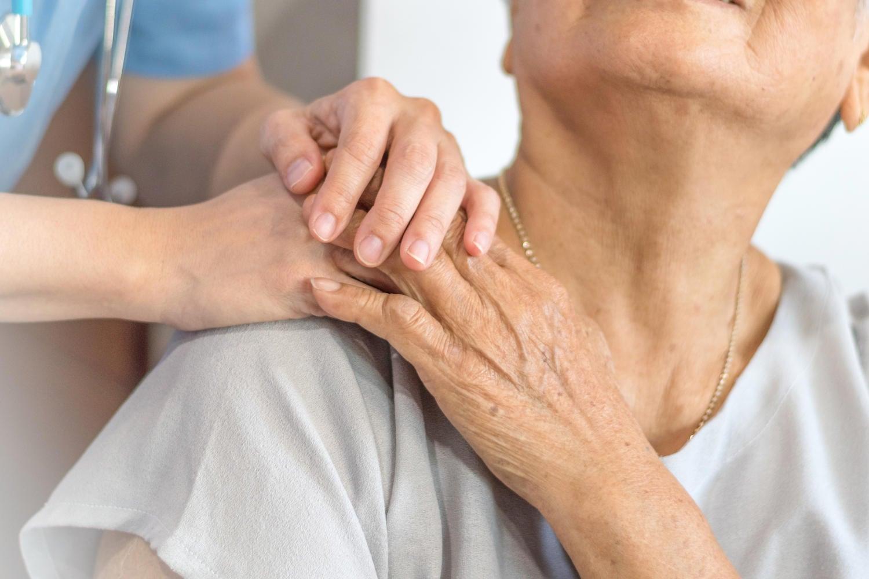 Dottoressa che prende la mano di un'anziana paziente