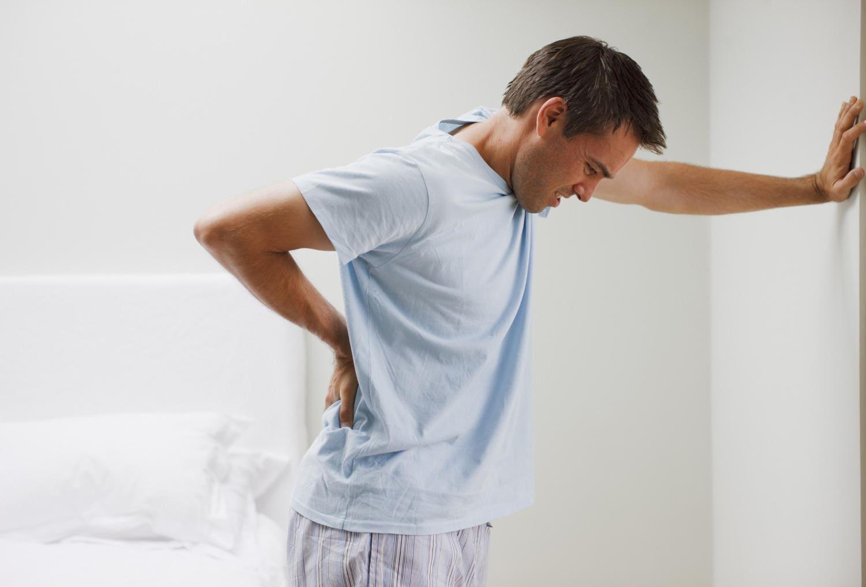 Uomo che si appoggia al muro a causa del dolore lombare alla schiena