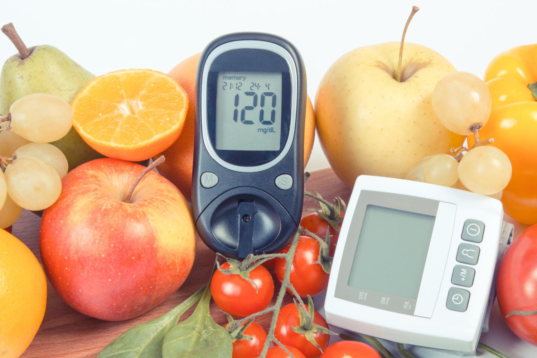 Glucometro che segna 120 mg/dL appoggiato su frutta e verdura