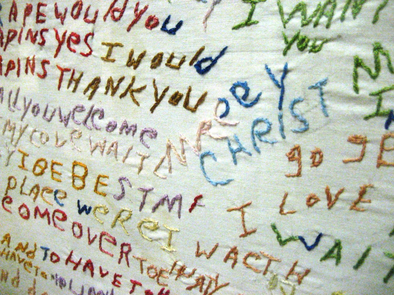 Tessuto bianco con un testo con parole ricamate in vari colori, ma prive di una connessione logica