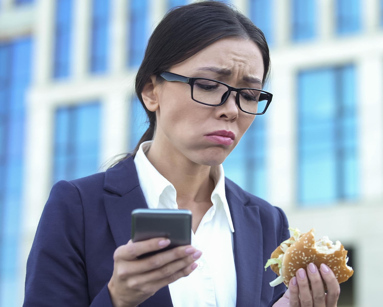 Donna che mangia junk-food mentre controlla il cellulare