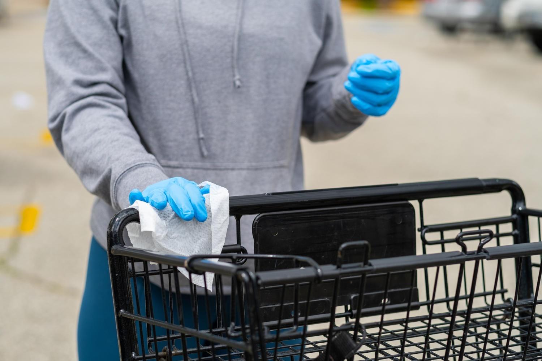 Donna che usa guanti e salvietta per spingere un carrello della spesa