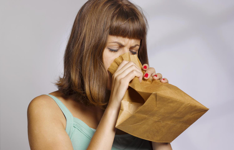 Donna che respira in un sacchetto di carta